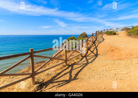 Wooden fence on cliff path on coast of Portugal in Algarve region near Praia de Marinha beach - Stock Photo