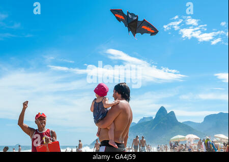 RIO DE JANEIRO - MARCH 10, 2013: A beach vendor selling kites displays his merchandise for a father and child on - Stock Photo