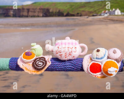 Yarn Bombing decorating public place with knitted objects here Bettys Teapot and Cakes on Saltburn Pier handrail - Stock Photo