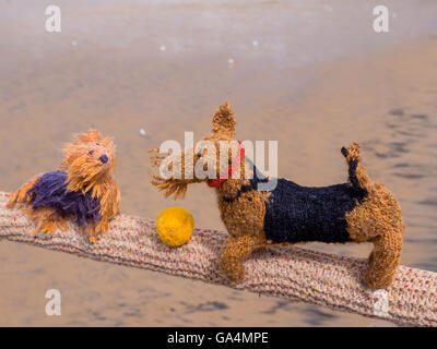 Yarn Bombing decorating public place with knitted objects here two Yorkshire Terrier Dogs on Saltburn Pier handrail - Stock Photo