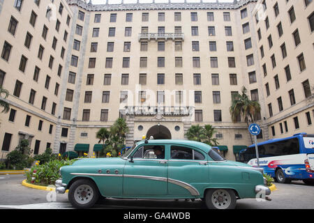 Front of famous Hotel Nacional de Cuba in Old Havana, with vintage American car used as a tax parked in front - Stock Photo
