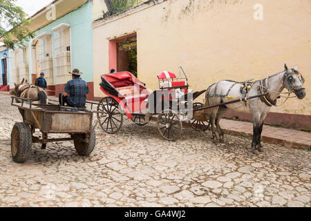 Horse-drawn cart for work and a fancier one for tourists on cobblestone street in Trinidad, Sancti Spiritus, Cuba, - Stock Photo