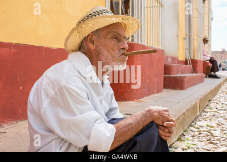 Local man in hat with cigar sitting on sidewalk in Plaza Major, Trinidad, Cuba - Stock Photo