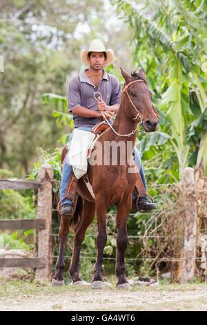 Handsome young cowboy on horseback at Hacienda La Belen, Cuba - Stock Photo