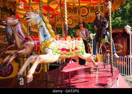 A young couple enjoying the fun of a Victorian Carousel in the City of York, England, UK - Stock Photo