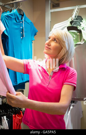 Sportswoman looking a polo shirt - Stock Photo