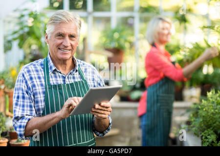 Senior man using digital tablet while woman working at greenhouse - Stock Photo