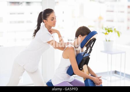 Masseuse giving back massage to woman - Stock Photo