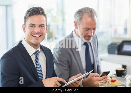 Two businessmen using digital tablet and mobile phone - Stock Photo