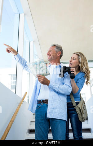 Man pointing while holding map with woman - Stock Photo