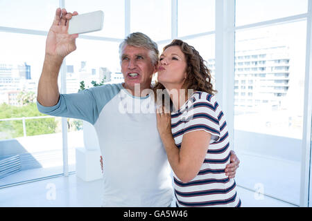 Couple taking selfie at restaurant - Stock Photo