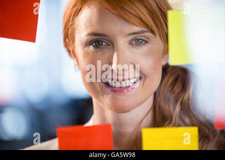 Portrait of pretty businesswoman seen through glass - Stock Photo