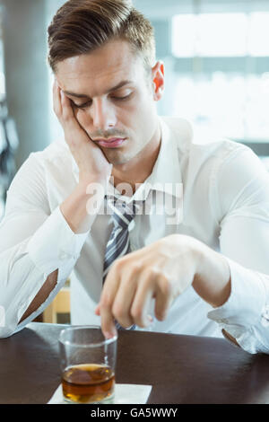 Depressed man looking at alcohol glass - Stock Photo