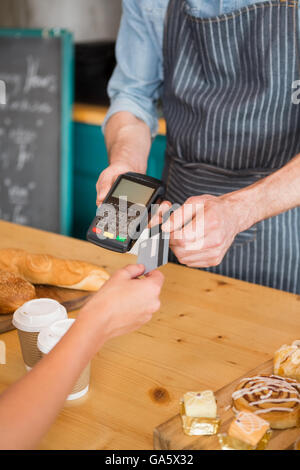 Woman making payment through credit card - Stock Photo