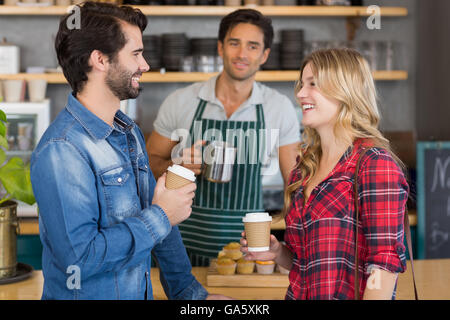 Happy couple standing at counter holding cup of coffee - Stock Photo