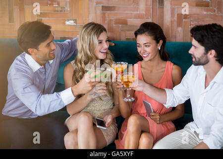 Group of friends toasting glasses of cocktail - Stock Photo