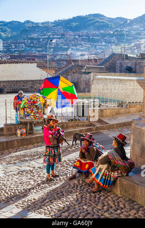 Three Peruvian women and animals at the end of the day spent posing with tourists in Cusco - Stock Photo