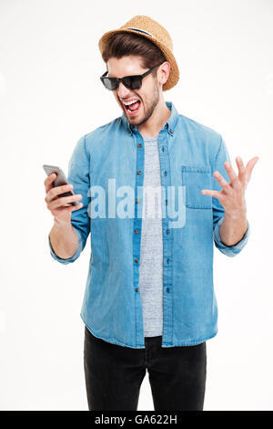 Close-up portrait of angry young man shouting at his smart phone isolated on white background - Stock Photo