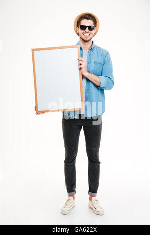 Close-up portrait of a smiling bearded man holding blank board isolated on the white background - Stock Photo