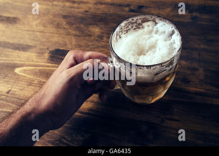 Hand holding beer mug full of cold fresh alcohol drink on wooden background, man in the bar, pov shot, selective - Stock Photo