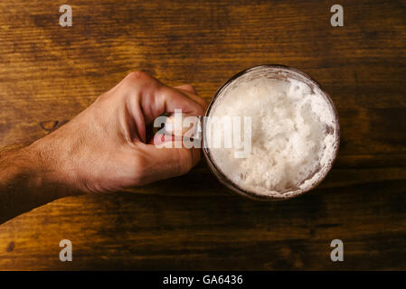 Hand holding beer mug full of cold fresh alcohol drink on wooden background, man in the bar, pov shot, top view, - Stock Photo