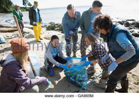 Beach cleanup volunteers picking up litter on beach - Stock Photo
