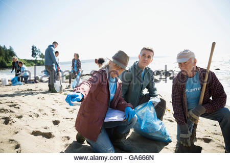 Beach cleanup volunteers picking up litter on sunny beach - Stock Photo