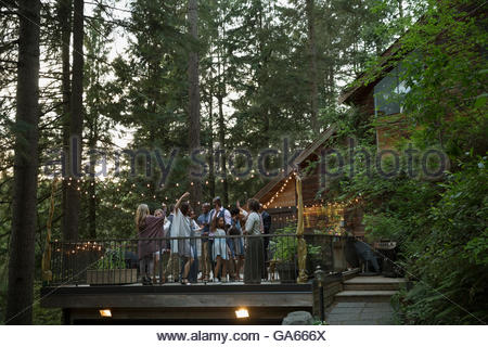 Friends dancing and enjoying party on cabin balcony in woods - Stock Photo