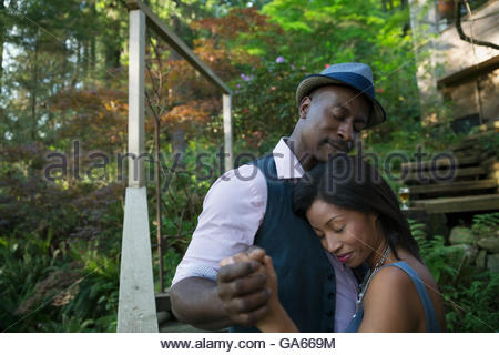 Serene affectionate couple dancing outside cabin in woods - Stock Photo