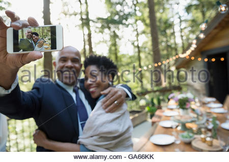Well-dressed couple taking selfie with camera phone on cabin balcony in woods - Stock Photo