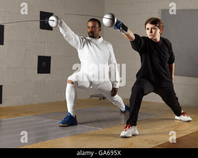 Coach and a teenage student practicing fencing in a gym - Stock Photo