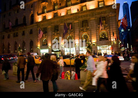 3 December 2006 - New York City, NY - Two women wait for a cab on the curb with bags of Christmas shopping on Fifth - Stock Photo