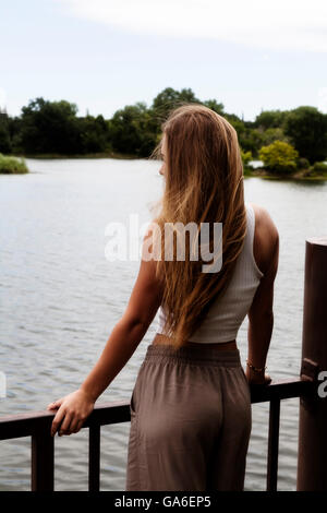 Caucasian Blond Teen Woman From Back Looking Out At River Holding On To Rail - Stock Photo