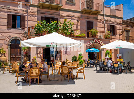 Visitors taking shade and refreshments in the village square of Forza D'Agro, Sicily, Italy - Stock Photo