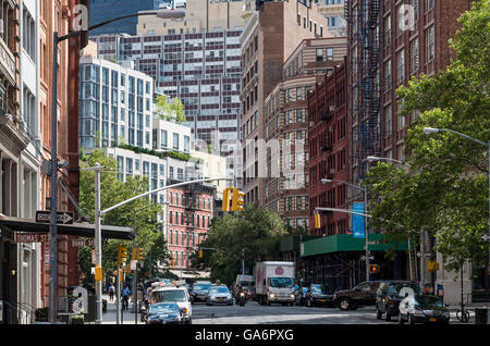 Street view along Hudson Street, Tribeca, with contrasting old and new buildings and skyscrapers with fire escapes - Stock Photo