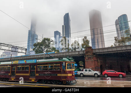 Melbourne CBD - Jun 4 2016: historical City Circle Tram and skyscrapers disappearing into the fog on cloudy rainy - Stock Photo