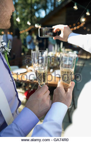 Homosexual couple taking selfie and drinking champagne at wedding reception - Stock Photo