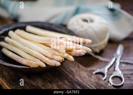 white asparagus in rustic bowl on wooden table - Stock Photo
