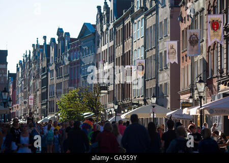 Summer crowds walk past terraced historical buildings and architecture on crowded Market street in downtown Gdansk, - Stock Photo