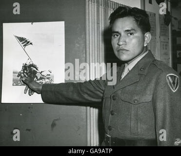 Marine Private First Class Ira Hayes illustrates the part he played in the raising of the Stars and Stripes on Mount - Stock Photo