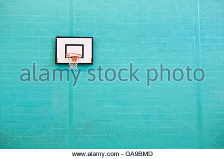 Basketball hoop hanging on turquoise brick wall in gym - Stock Photo