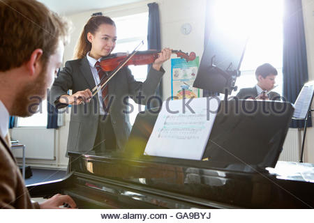 Middle school students and teacher playing musical instruments in music class - Stock Photo