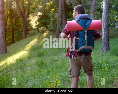 Man with backpack exploring mountains - Stock Photo