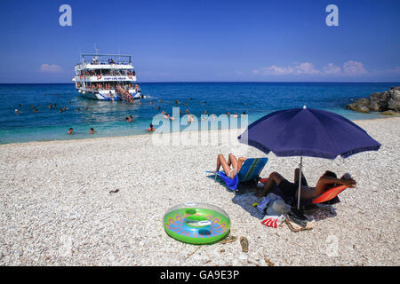 Tourists enjoy a summer evening at Xigia beach as a boat with other tourists approaches in Zakynthos on July 25, - Stock Photo