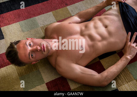 Cool dark-haired shirtless muscular handsome young man laying on the floor over colorful rug, looking at camera, - Stock Photo