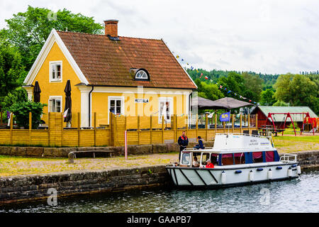 Motala, Sweden - June 21, 2016: Small yellow house with the text Motala on the facade. Chartered boat moored outside - Stock Photo