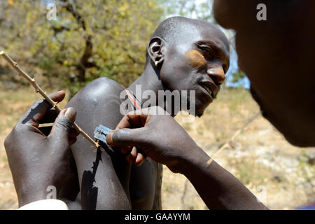 Men from the Mursi tribe decoratively scaring skin, one man scars the arm of another one by lifting the skin with - Stock Photo