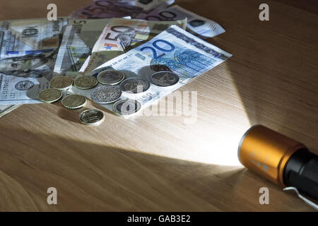 In a dark room a beam of light of the electric lantern lights money lying on the table. - Stock Photo
