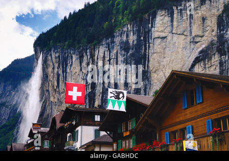 Houses in Lauterbrunnen (Switzerland) and Staubbach Falls - Stock Photo