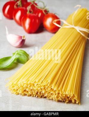 Spaghetti pasta, tomato, garlic and basil leaves on grey stone table - Stock Photo